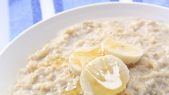 A bowl of warming porridge, with banana and honey.  Traditional Scottish oatmeal.